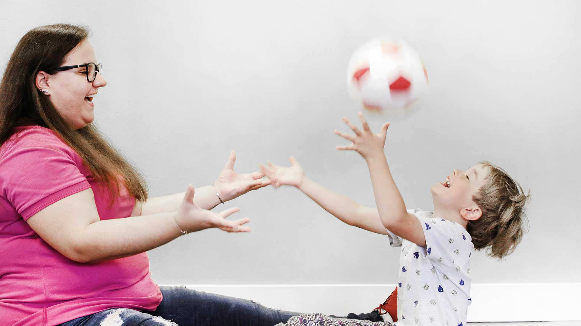 Arzthelferin spielt Ball mit Kind
