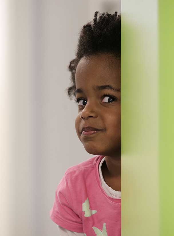 Mädchen lugt hinter einer Wand hervor